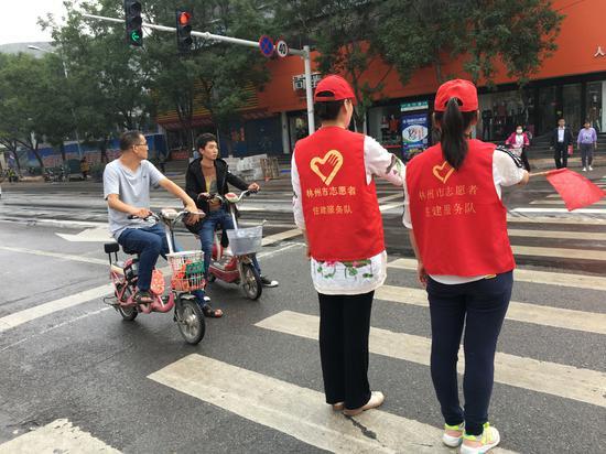 为引导市民文明出行,助力我市文明城市创建。9月5日,林州市住建局4名志愿者到太行路与龙山街交叉口,开展文明交通志愿服务活动。  文明交通志愿服务活动  志愿者为市民指路  志愿者冒雨坚守岗位   此次活动,不仅充分展现了住建队伍良好的精神风貌,也以实际行动助推了我市文明城市创建工作。   活动中,志愿者们头戴小红帽,身穿印有住建服务队的红马甲,手持交通引导旗,分别站在十字路口的四个方向针对非机动车、行人乱闯红灯等交通违法行为进行引导,红灯亮,红旗起,绿灯亮,红旗落,在引导旗的起落之间,龙山路口的交通