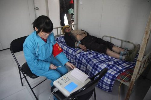 志愿者为农民工做心电图健康检查